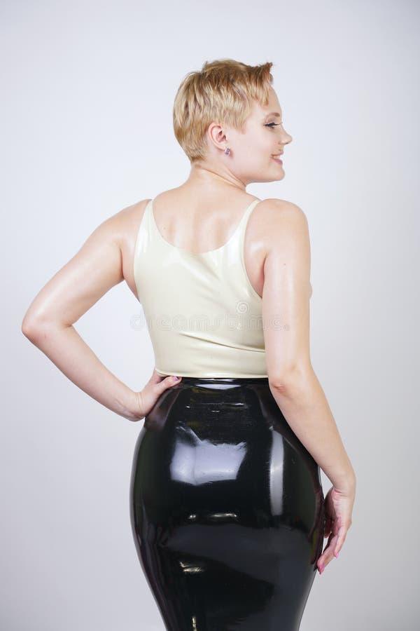 Fille blonde de cheveux rouverains avec la robe en caoutchouc de port de latex de corps sinueux sur le fond blanc de studio photo libre de droits