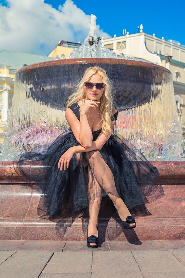 Fille blonde de mode s'asseyant sur le banc près de la fontaine Rue Fashi image stock