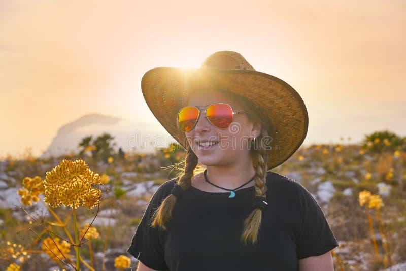 Fille blonde de pays avec des lunettes de soleil au coucher du soleil image libre de droits