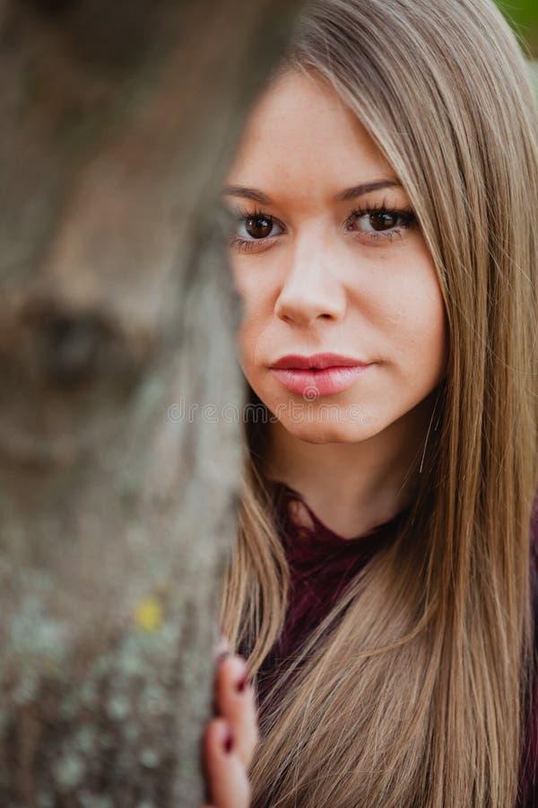 Fille blonde de portrait à côté d'un tronc d'arbre images libres de droits