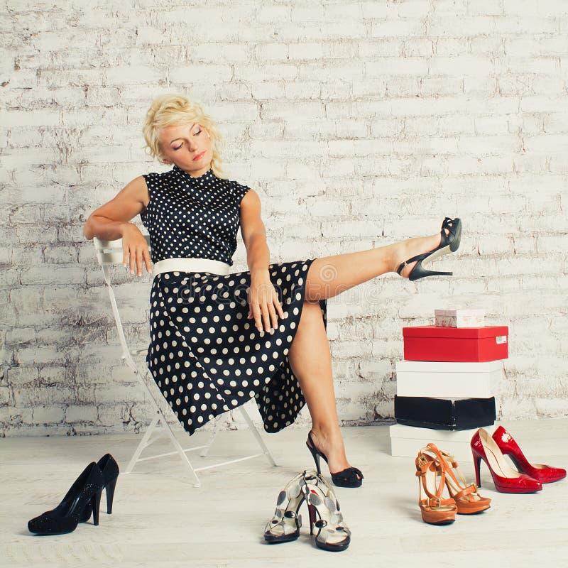 Fille blonde de Shopaholic dans la robe se reposant avec des chaussures image stock