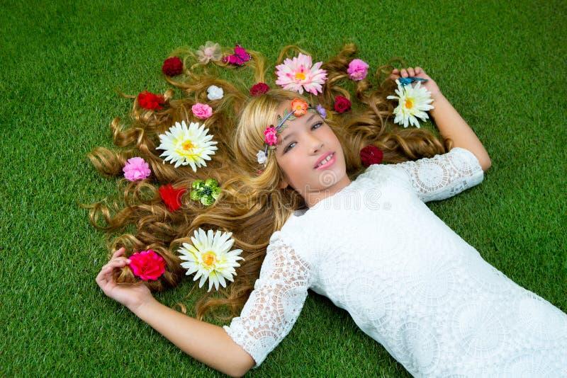 Fille blonde de source avec des fleurs sur le cheveu au-dessus de l'herbe photo libre de droits