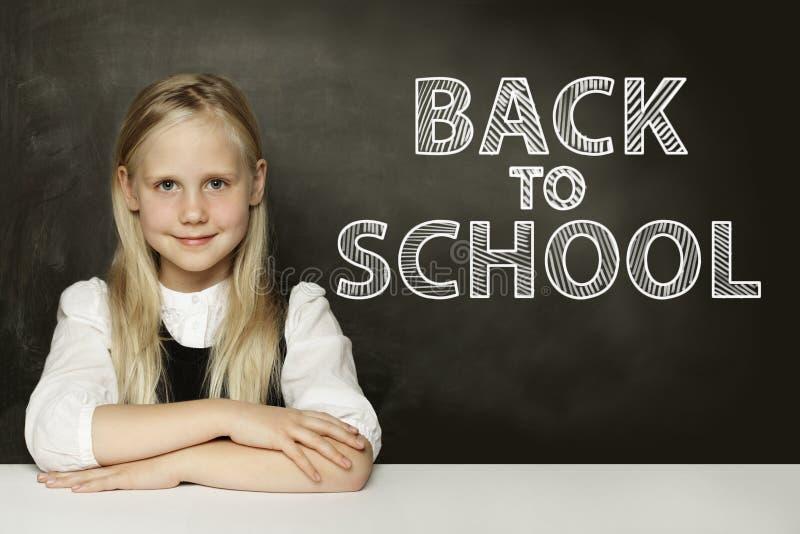 Fille blonde de sourire d'enfant pensant sur le tableau De nouveau ? l'?cole photos libres de droits