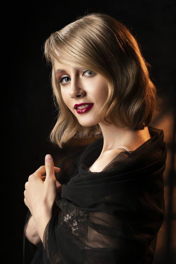 Fille blonde de sourire de visage mignon avec la coiffure de style de cru, portant une robe de scintillement d'or et un voile noi image stock