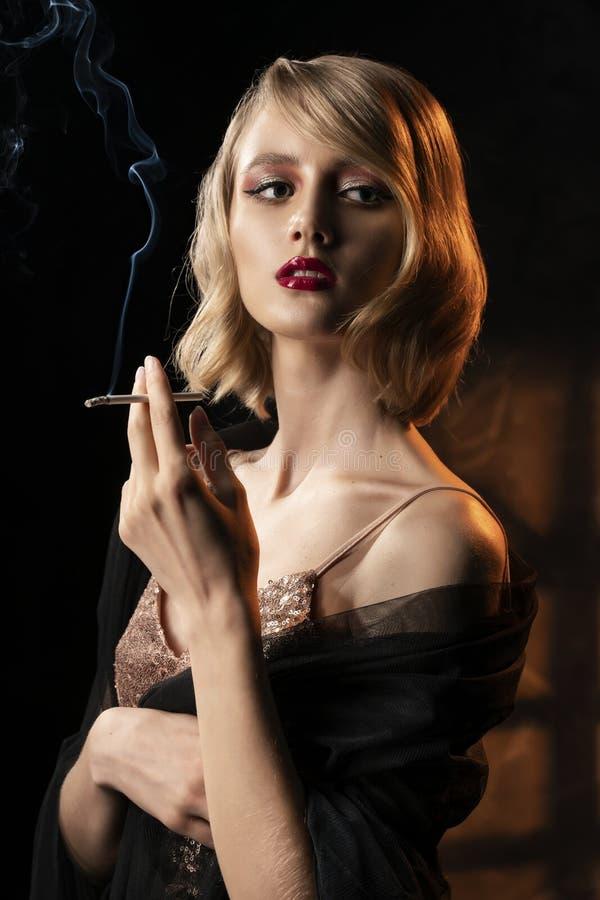 Fille blonde de visage mignon avec la coiffure de style de cru, portant une robe de scintillement d'or et un voile noir sur ses ? photos stock