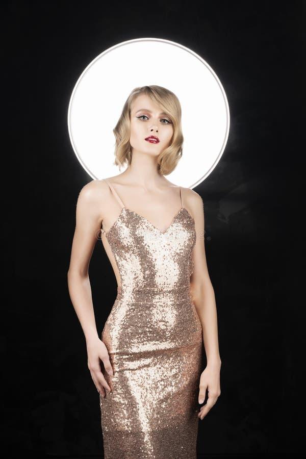 Fille blonde de visage mignon avec les l?vres rouges et la coiffure de style de cru, portant une robe de scintillement d'or avec  photo libre de droits