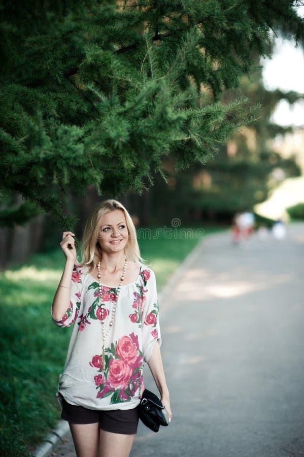 Fille blonde en broderie près d'un fourrure-arbre sur une promenade image libre de droits