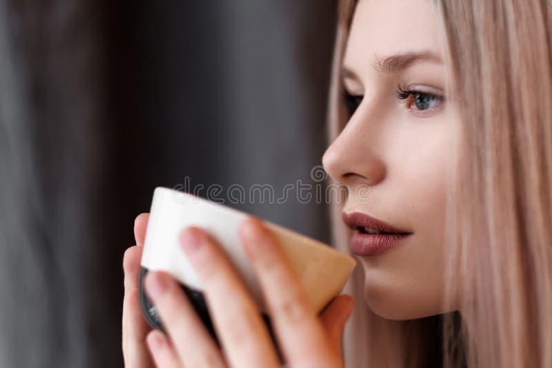 Fille blonde en gros plan avec une tasse de boisson, de thé ou de café chaud, à la maison dans une salle confortable images libres de droits