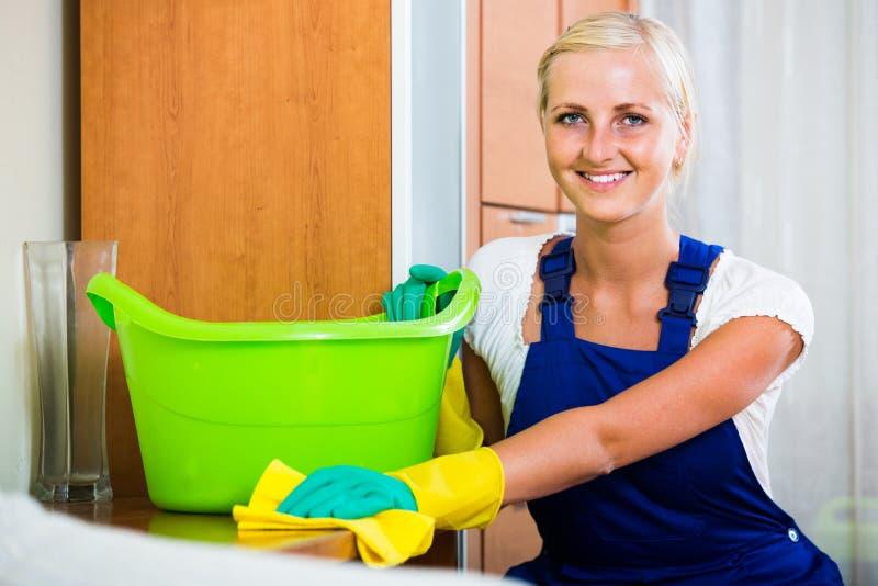 Fille blonde en saupoudrage uniforme dans la chambre et le sourire image libre de droits