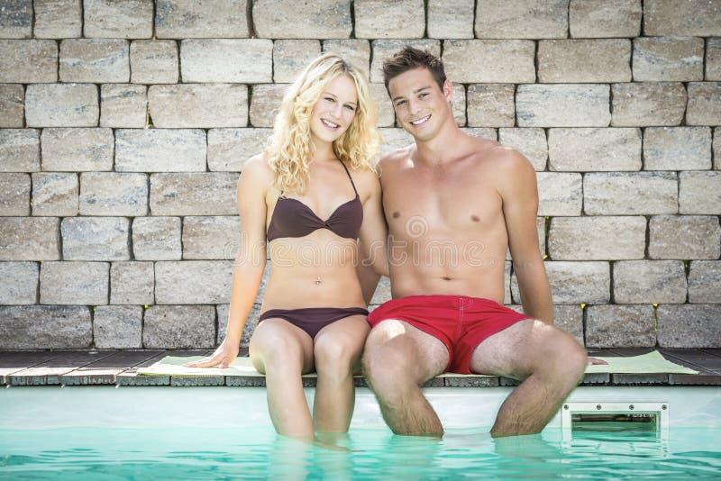 Fille blonde et garçon beau sur la piscine image libre de droits