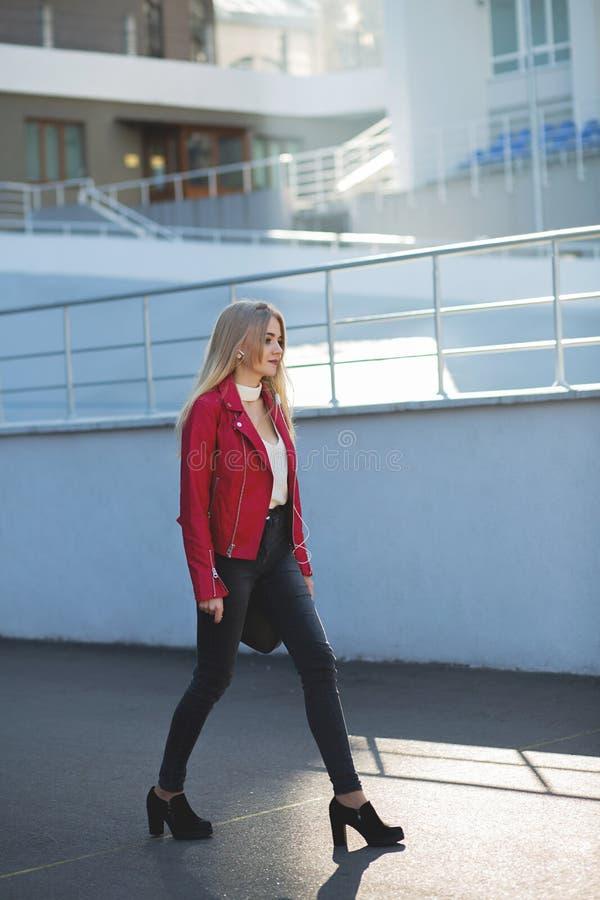 Fille blonde fabuleuse utilisant la veste rouge descendant la rue avec la lumière du soleil images stock