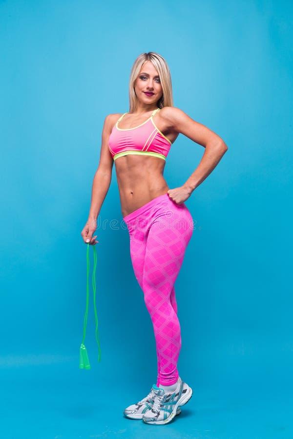 Fille blonde folâtre dans les vêtements de sport roses avec la corde à sauter sur le fond bleu dans le studio photo libre de droits
