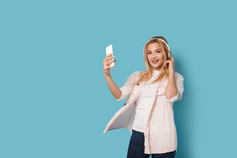 Fille blonde gaie avec le sourire de smartphone images stock
