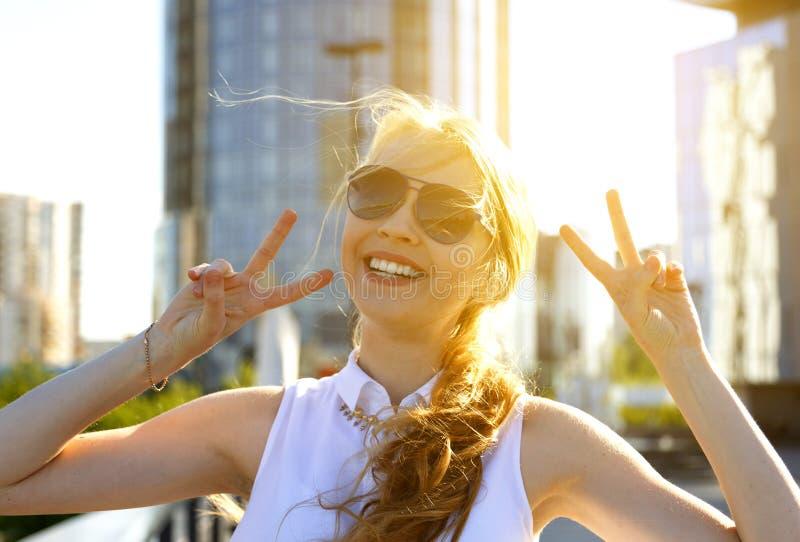 Fille blonde heureuse de sourire montrant la double position de v-signe dans la rue de ville sous des rayons de soleil photos libres de droits