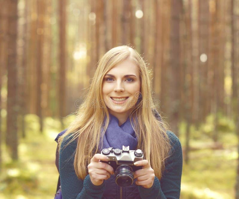 Fille blonde heureuse et belle prenant des photos dans le camp de forêt, tou images stock