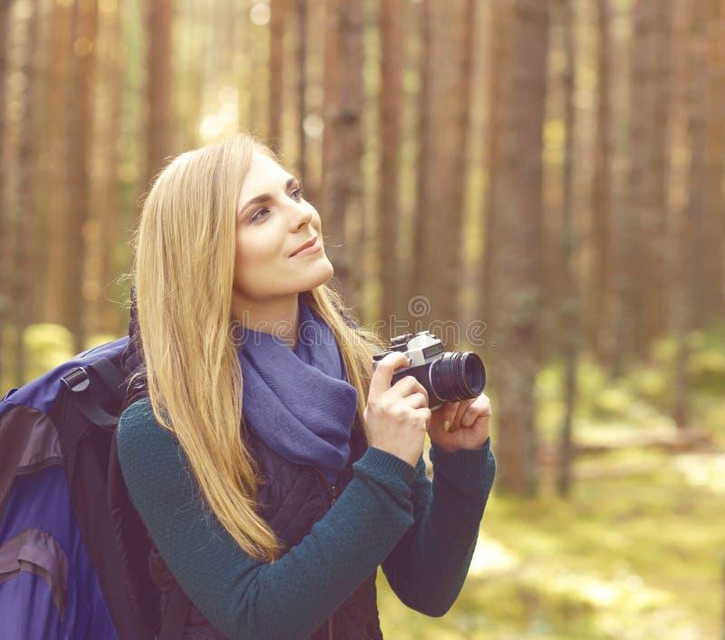 Fille blonde heureuse et belle prenant des photos dans le camp de forêt, tou photo libre de droits