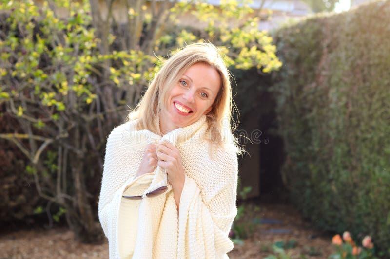 Fille blonde joyeuse attirante heureuse dans le plaid tricoté en ivoire souriant et regardant la caméra dehors dans le jardin photos stock