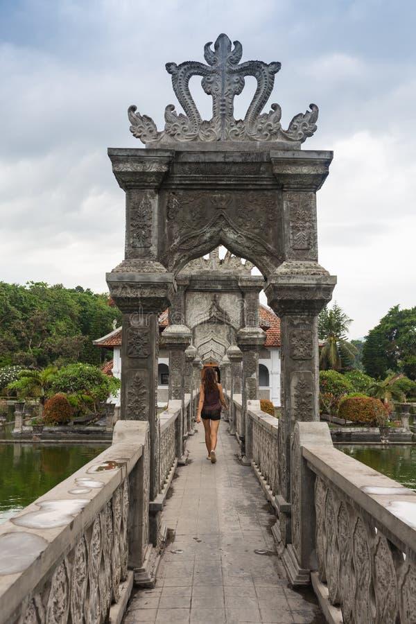 Fille blonde marchant loin sur un pont en pierre dans le temple hindou historique de Bali, entouré par l'eau photos libres de droits