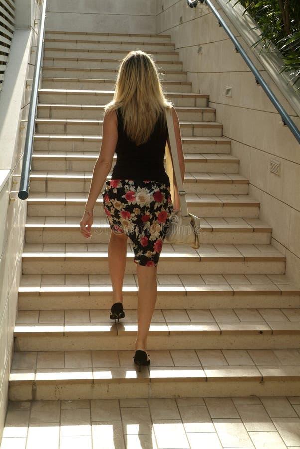 Fille blonde marchant sur des escaliers photos libres de droits