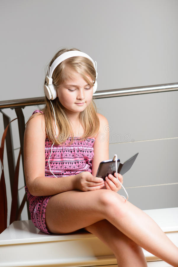 Fille blonde mignonne écoutant la musique photos libres de droits