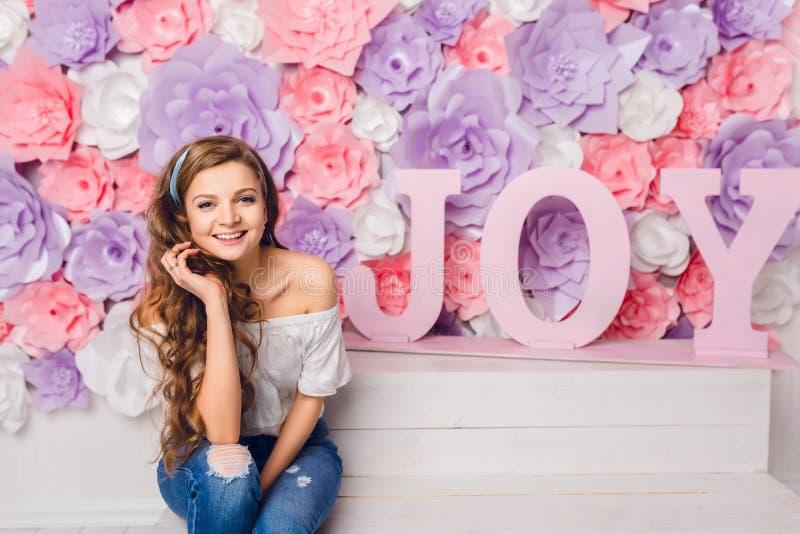 Fille blonde mignonne s'asseyant sur un banc dans un studio souriant largement Elle a de longs cheveux bouclés et porte des blues photographie stock libre de droits