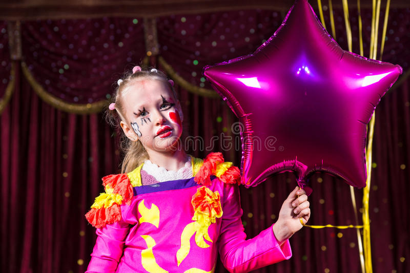 Fille blonde mignonne tenant un ballon en forme d'étoile photo stock