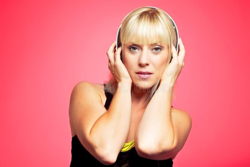 Fille blonde retenant l'écouteur sur sa tête photos stock