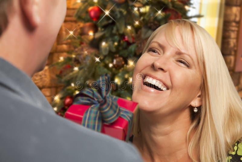 Fille blonde riante échangeant des cadeaux devant l'arbre de Noël photos stock