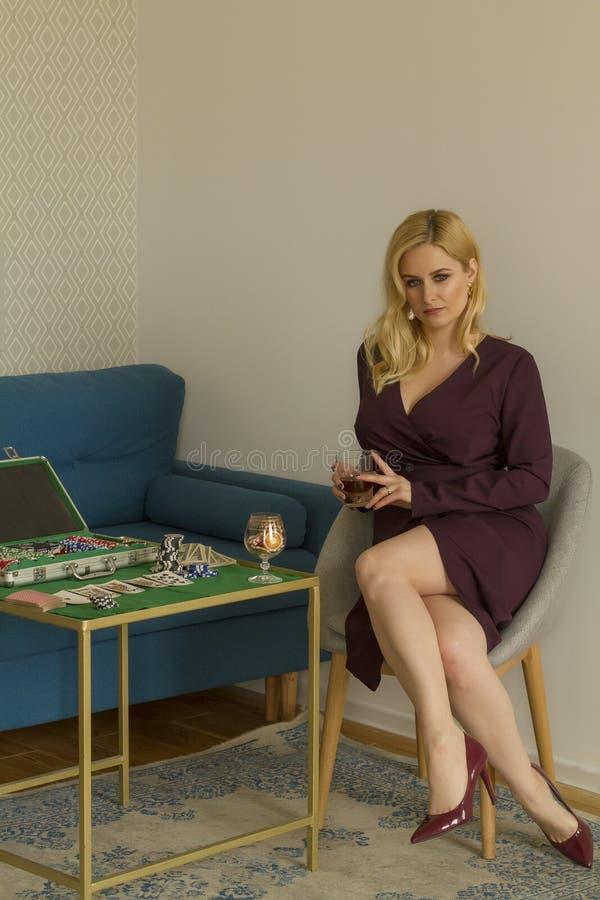 Fille blonde s'asseyant avec un ensemble de tisonnier photos libres de droits