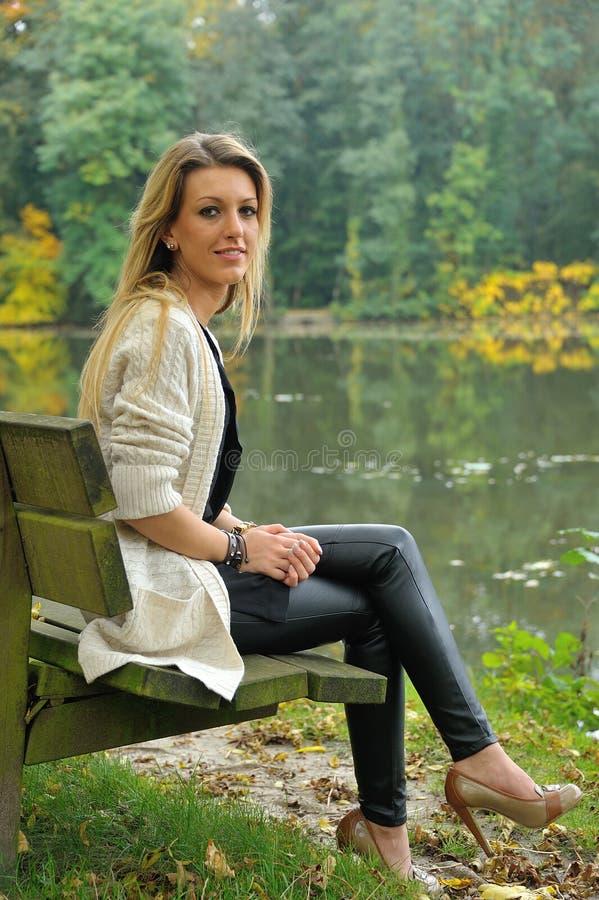 Fille blonde s'asseyant sur le banc à côté du lac image libre de droits