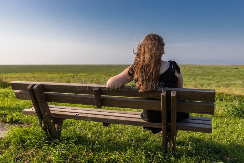 Fille blonde s'asseyant sur un banc photo libre de droits