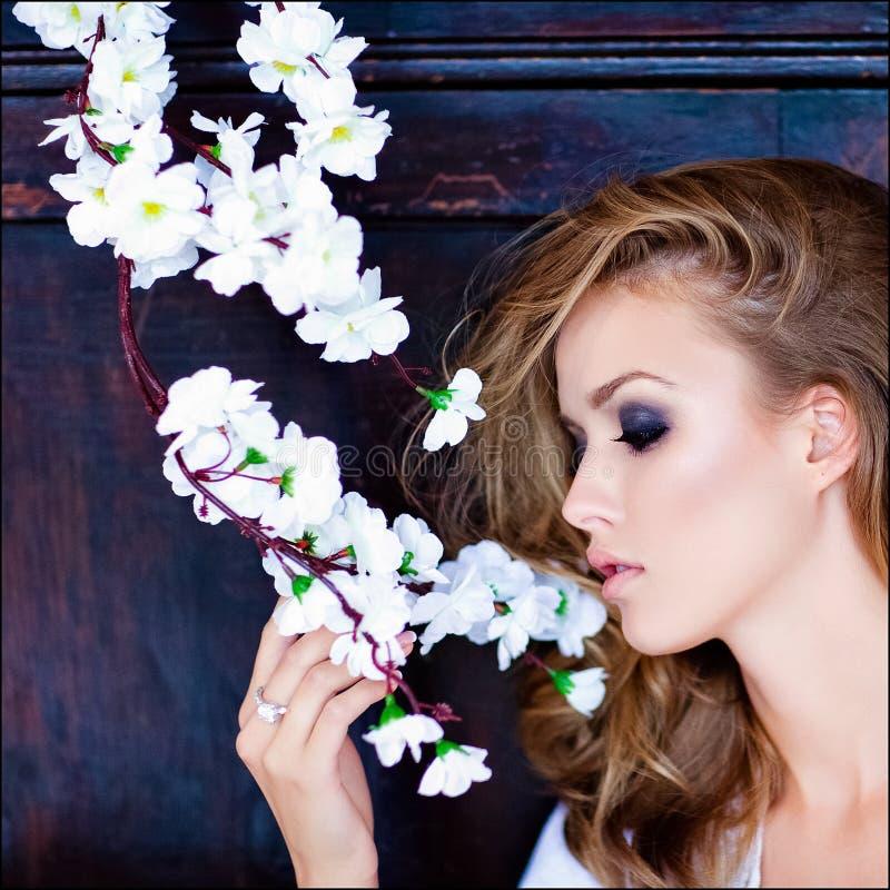 Fille blonde sensuelle de plan rapproché de portrait avec des yeux bleus avec Sakura images libres de droits