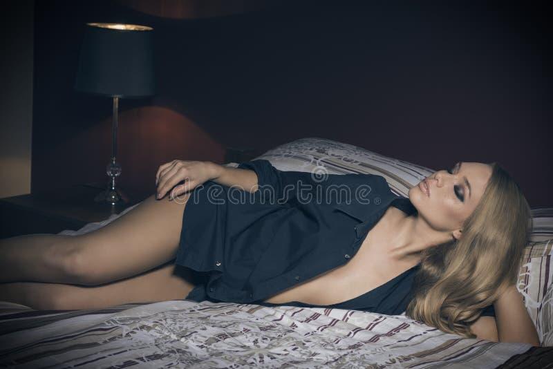 Fille blonde sensuelle se trouvant sur le lit photos stock