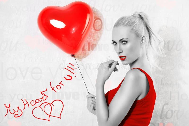 Fille blonde sexy avec le ballon de coeur en noir et blanc photographie stock libre de droits