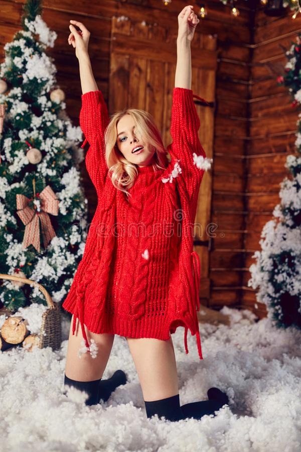 Fille blonde sexy dans le chandail rouge, ayant l'amusement et posant contre le contexte du décor de Noël Arbre d'hiver et de Noë photographie stock