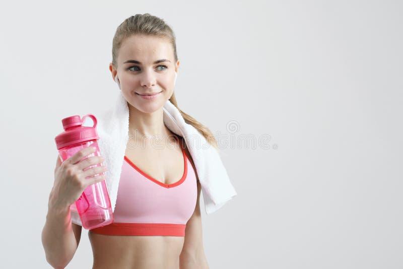 Fille blonde sportive avec une serviette blanche autour de son cou, dans les v?tements de sport rouges et avec les ?couteurs sans images stock