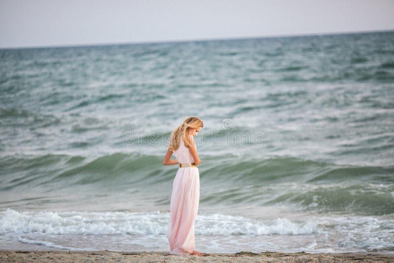 Fille blonde sur le bord de la mer photographie stock libre de droits
