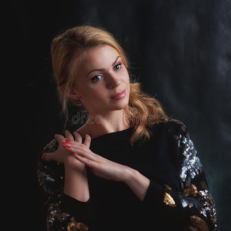 Fille blonde sur un fond foncé photographie stock libre de droits