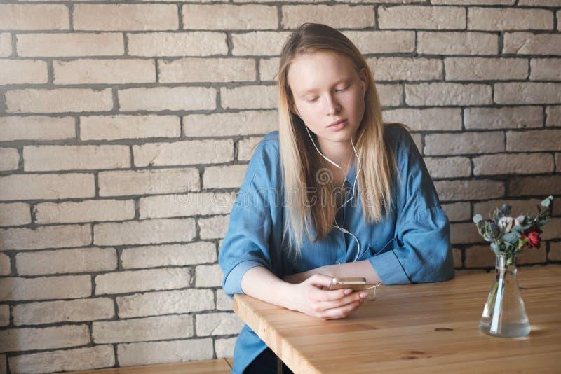 Fille blonde triste dans le chemisier bleu se reposant à la table dans un café, l image stock