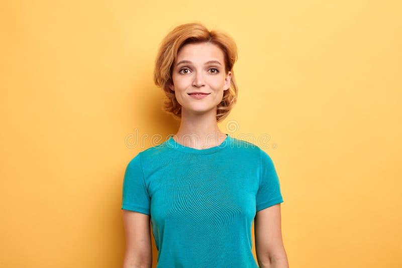 Fille blonde utilisant le T-shirt élégant bleu et regardant la caméra photo libre de droits