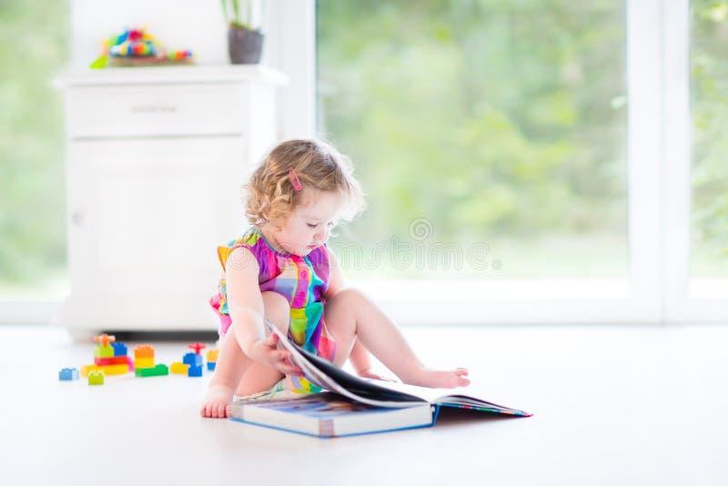 Fille bouclée adorable d'enfant en bas âge lisant un livre photographie stock
