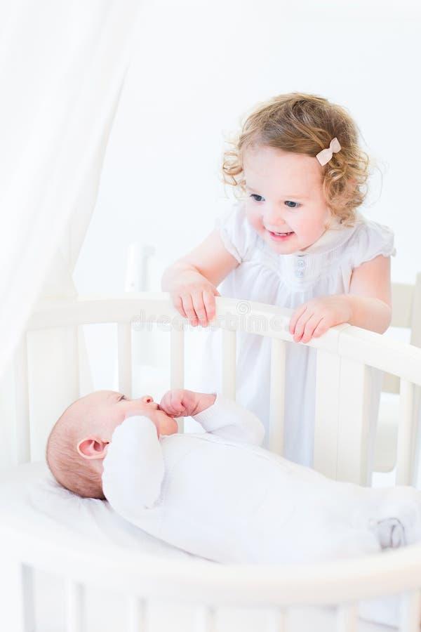 Fille bouclée adorable d'enfant en bas âge parlant au frère nouveau-né photos stock