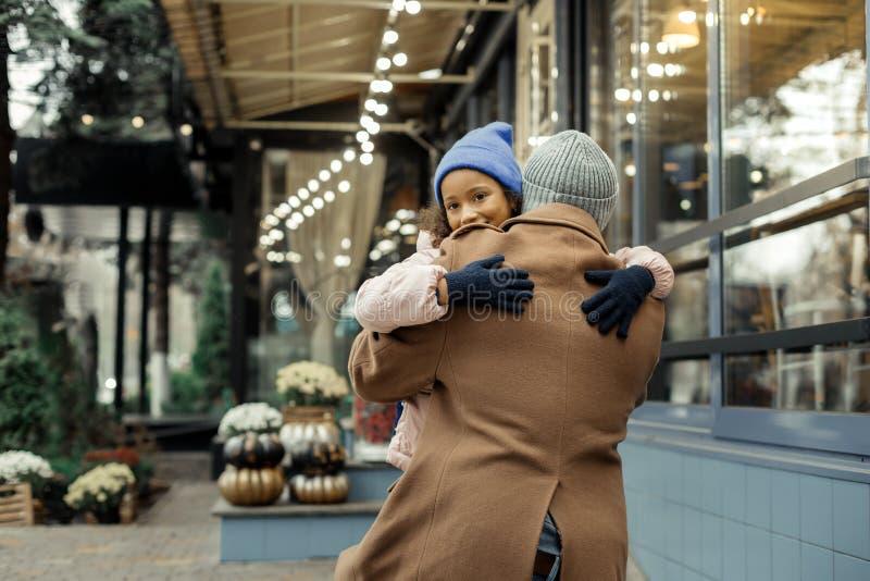 Fille bouclée aux yeux noirs mignonne utilisant le chapeau bleu étreignant son père photographie stock libre de droits