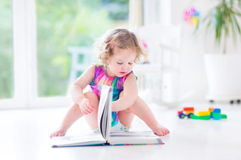 Fille bouclée drôle d'enfant en bas âge dans le livre rose de lecture de robe photos libres de droits