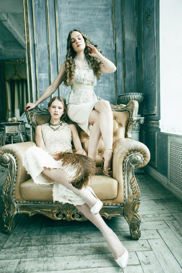 Fille boucl?e blonde de coiffure de la soeur assez jumelle deux dans l'int?rieur de luxe de maison ensemble, concept riche des je photographie stock