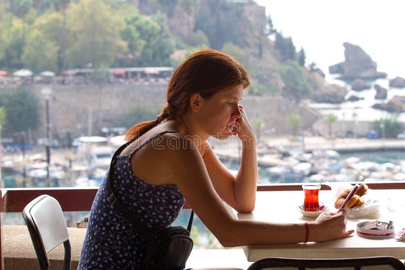 Fille bouleversée de tristesse s'asseyant en café et poussant des feuilles par un téléphone intelligent Antalya, vieille ville de photo libre de droits