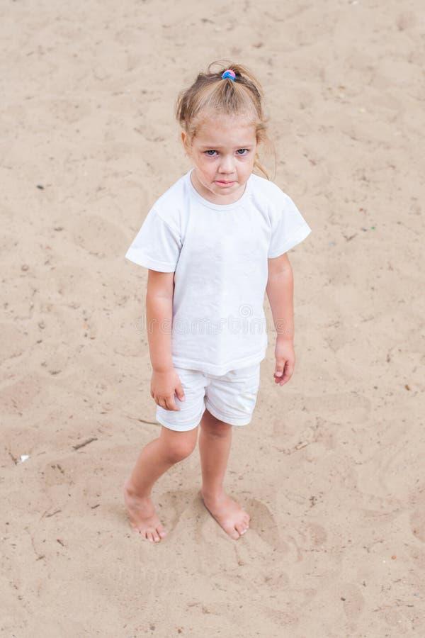 Fille bouleversée se tenant sur le sable image stock