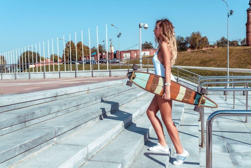 Fille bronzée dans un corps blanc, descendant les escaliers en été dans la ville Dans la main d'une planche à roulettes, longboar images stock