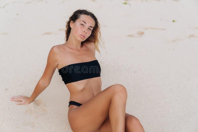 Fille bronzée sexy dans le maillot de bain posant et prenant un bain de soleil le jour ensoleillé chaud à la plage sablonneuse photos libres de droits