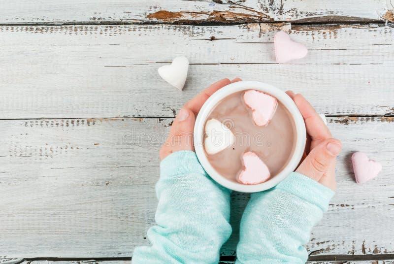 Fille buvant du chocolat chaud avec des coeurs du ` s de guimauves photographie stock libre de droits